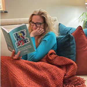reading list image of Sarah McVanel reading a book under a blanket