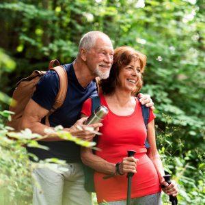 awe walk image of elderly couple walking in nature