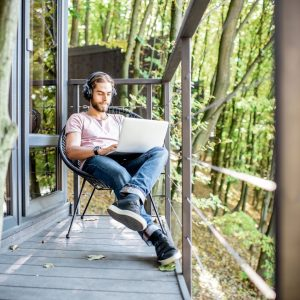 man in woods with laptop on lap doing remote work