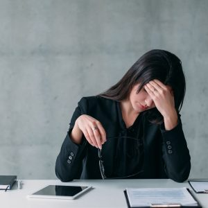 woman at desk with hand on forehead experiencing a crisis of confidence