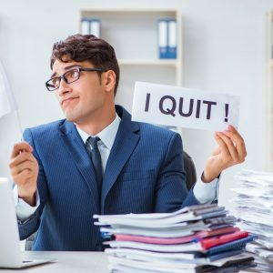 The great resignation with Sarah McVanel image of man holding I Quit sign at his desk