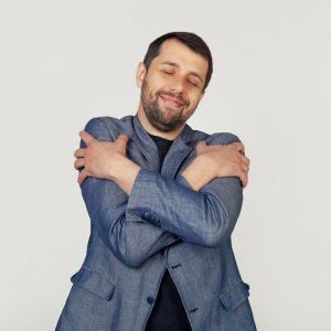 man hugging himself to get over crisis of confidence
